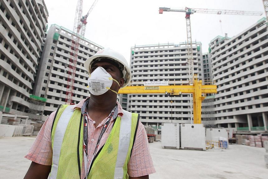 A worker wearing a N95 mask as prevention against haze while working at a construction site.