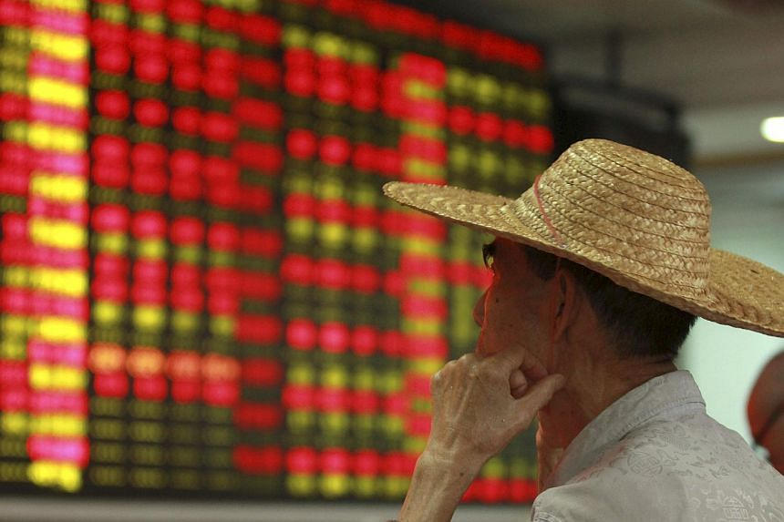 An investor looks at an electric board showing stock information at a brokerage house in Haikou, Hainan province, China.