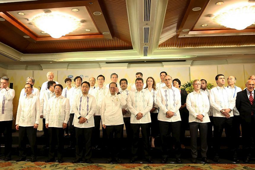 Philippine President Benigno Aquino (front 5th Left) adjusts his glasses as he stands next to Finance Secretary Cesar Purisima (front 4th Left) while posing for a group picture with the APEC Heads of Delegations and the APEC Secretariat Executive Dir