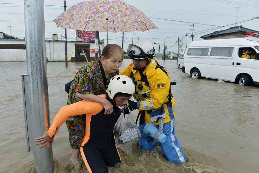 A woman being rescued by police officers in Joso in Japan's Ibaraki prefecture on Sept 10, 2015, after Typhoon Etau hit.