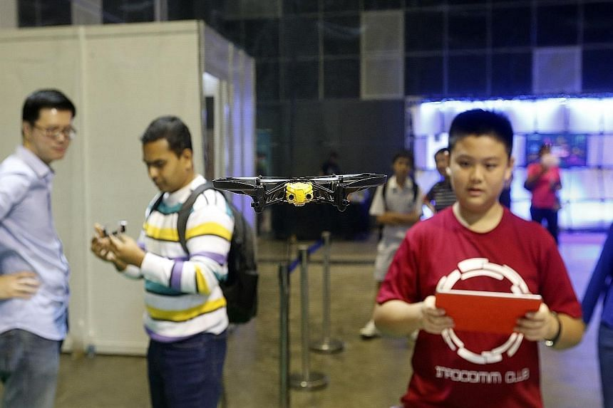 "Tse Chung Man, 14, flying a mini-drone in the ""Drone Zone"" at the Infocomm Development Authority's Young Tech Fest. Other visitors were there to try out different technologies or take part in free workshops."