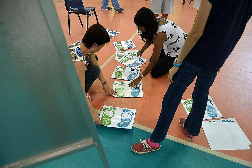 Election officers setting up the polling station yesterday at Pei Chun Public School. Their tasks ranged from arranging tables in neat rows (left) to putting up posters (above) giving reminders. Across the island, many schools and void decks will tur