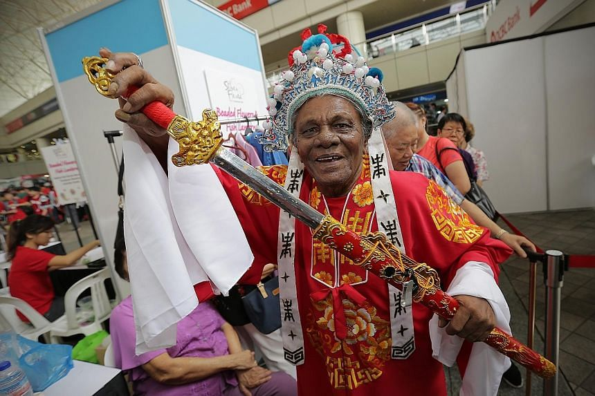 Mr Nagore Allauddeen Ibrahim, 79, trying on a Teochew opera costume at a photobooth set up by the Young Men's Christian Association at its Silver Fiesta to promote active ageing through the arts. More than 700 seniors took part in activities such as