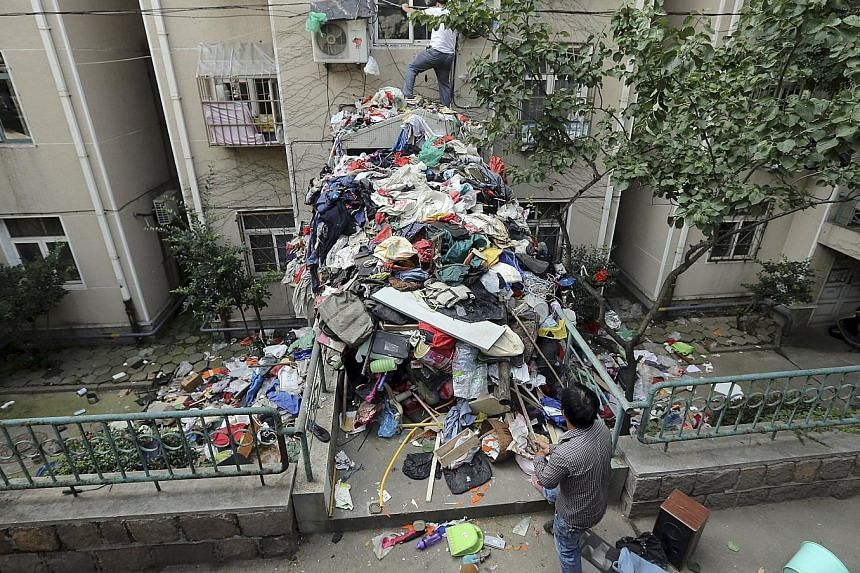A pile of garbage blocks an entrance to an apartment building in Qingdao, Shandong province, in eastern China as workers clean up one of the units. The authorities started cleaning out the elderly woman's home on Wednesday, with the help of her son,