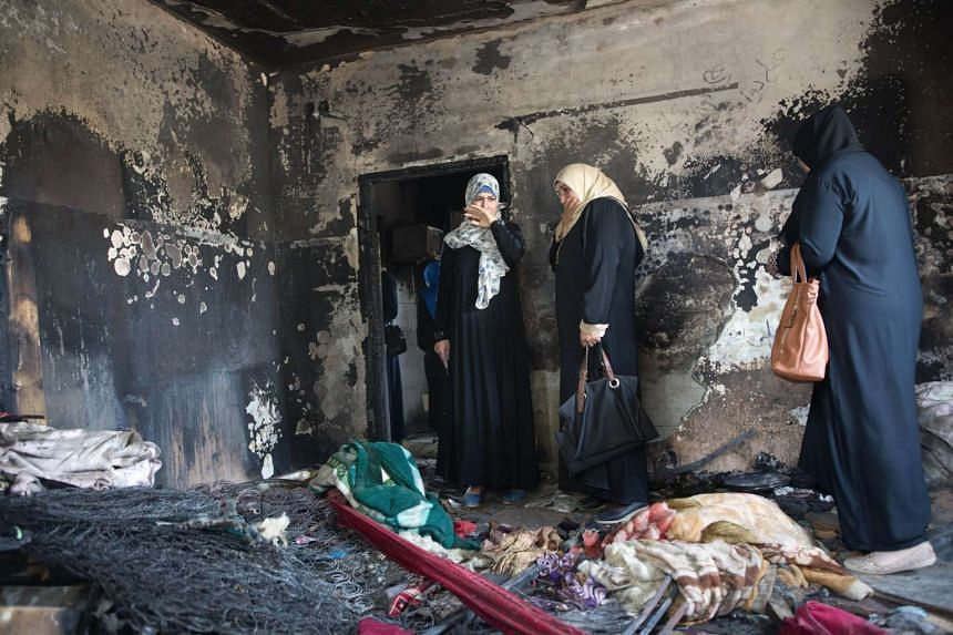 Palestinian women look at the damage at the Dawabsha family's home in the West Bank village of Duma on Aug 4, 2015.