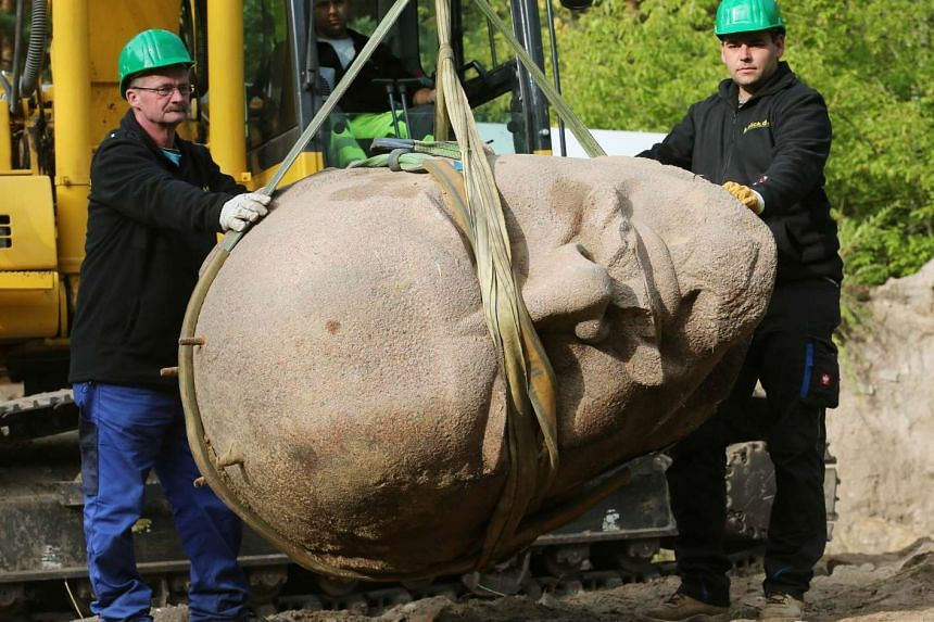 Workers remove the head of a statue of the late Soviet leader Lenin.