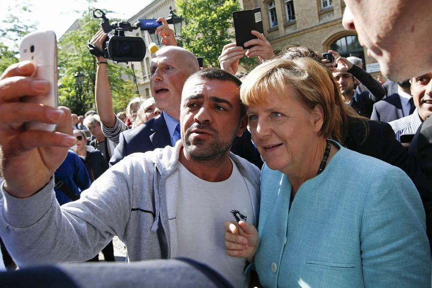 A migrant takes a selfie with German Chancellor Angela Merkel.