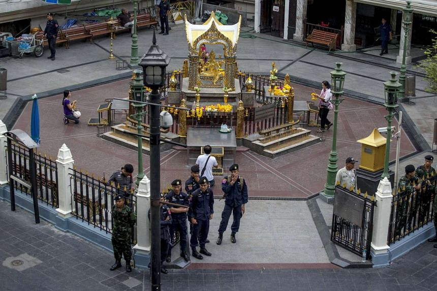 Thai police stand guard as people pray during a crime re-enactment near the bomb site at Erawan shrine in central Bangkok, Thailand on Sept 9, 2015.