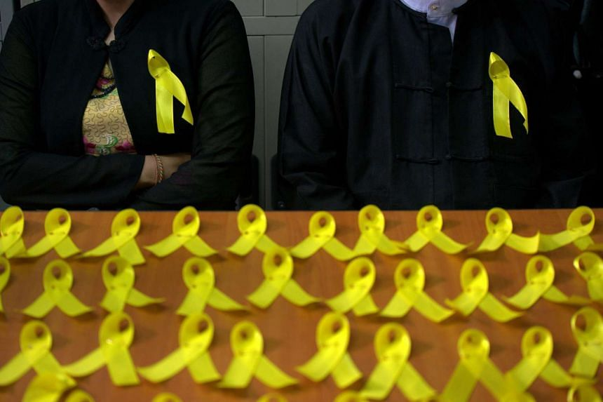 Myanmar lawyers wear yellow ribbons pinned to their jackets, a new symbol of defiance as public servants increasingly voice opposition to the military's dominance of public services, as part of a campaign in Yangon on Sept 11, 2015.