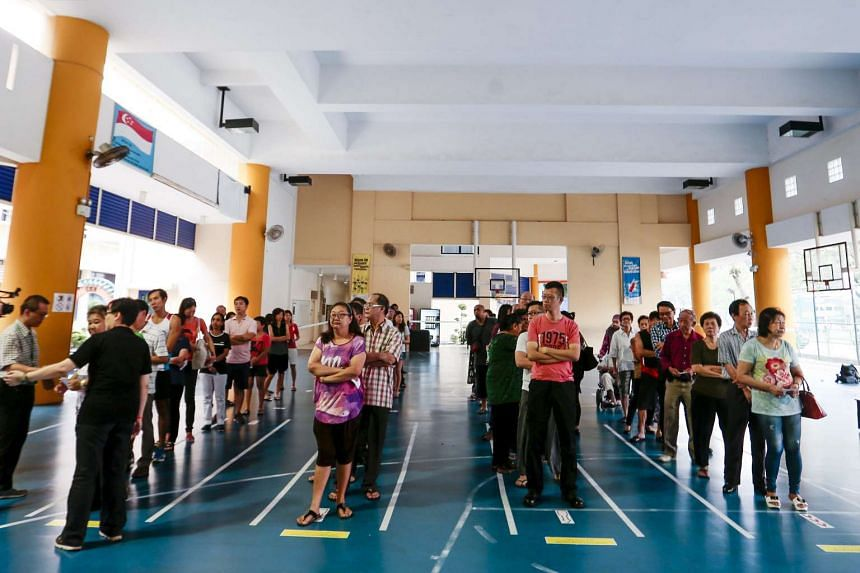 Singaporeans queue to cast their vote at a polling station on Sept 11, 2015.