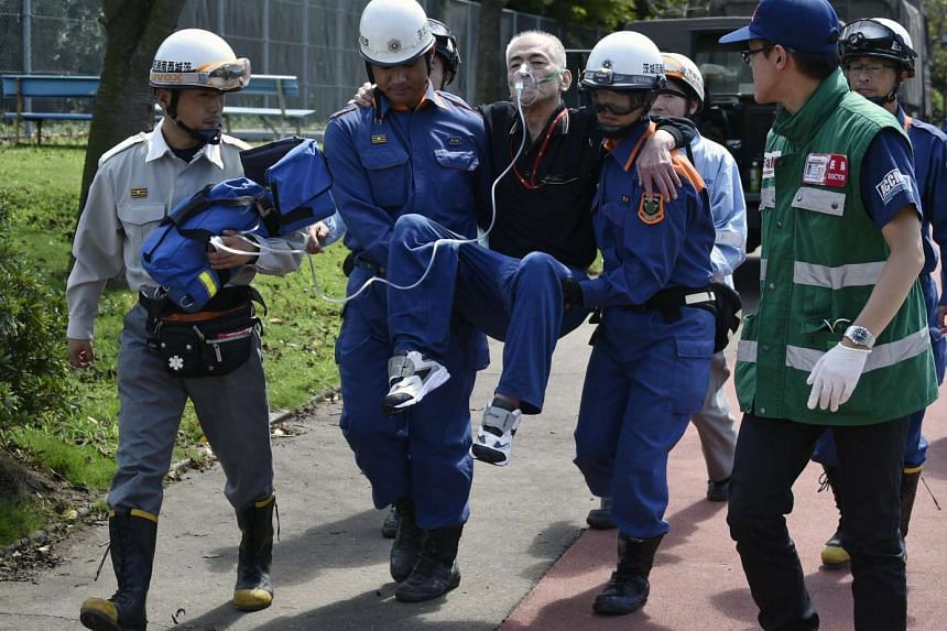 A man is carried after being rescued from a flooded area after the Kinugawa River breached its banks on Sept 10, due to heavy rain generated by typhoon Etau in Joso, Ibaraki prefecture, north-east of Tokyo, Japan on Sept 11, 2015.