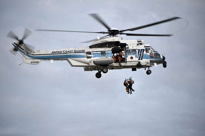 Japan Coast Guard personel are lifted back to their helicopter after the rescued people stranded in a flooded area after the Kinugawa River breached its banks on Sept 10, due to heavy rain generated by typhoon Etau in Joso, Ibaraki prefecture, north-