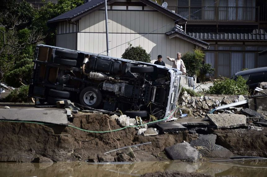A car lies on the side after the Kinugawa River breached its banks on Sept 10, due to heavy rain generated by typhoon Etau in Joso, Ibaraki prefecture, north-east of Tokyo, Japan on Sept 11, 2015.