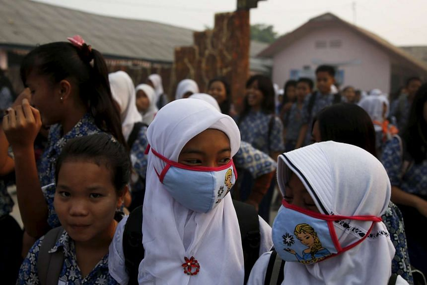 Students, wearing face masks, walk in front of their school as they prepare to head home due to the unhealthy quality of air in Palembang, on Indonesia's Sumatra island on Sept 10, 2015.