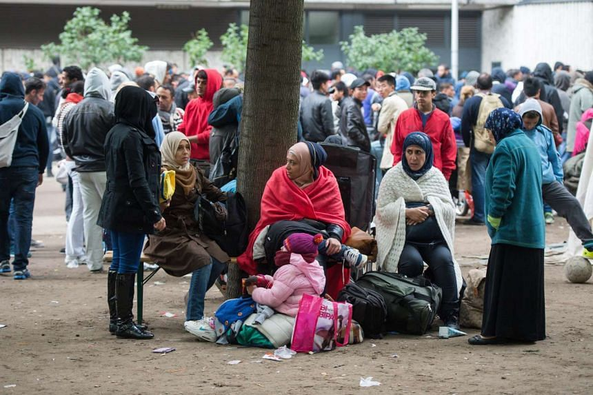 Refugees wait outside the Berlin State Office for Health and Social Affairs in Berlin, Germany, Sept 11, 2015.