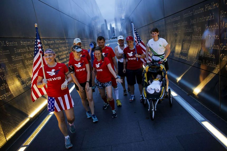 Members of the Red White and Blue team walk through the 9/11 Empty Sky memorial after posing for a picture at sunrise across from New York's Lower Manhattan and One World Trade Center, in Liberty State Park in Jersey City, New Jersey, on Sept 11, 201