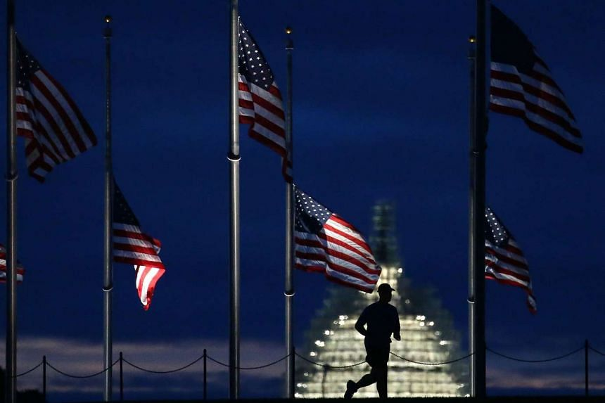 A man jogs past a row of American flags that have been lowered to half staff on the Washington Monument grounds, near the US Capitol on Sept 11, 2015 in Washington, DC.