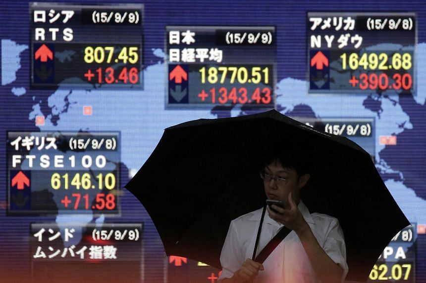 A pedestrian holding an umbrella holds a mobile device in front of an electronic stock board displaying the closing figure of the Nikkei 225 Stock Average outside a securities firm in Tokyo, Japan, on Sept 9, 2015.