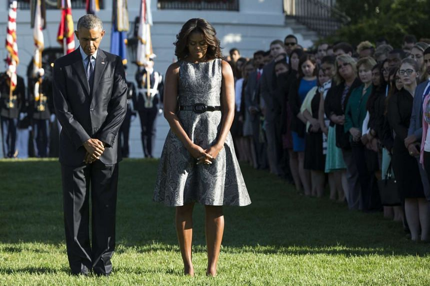 US President Barack Obama and First Lady Michelle Obama observe a moment of silence on the South Lawn of the White House in Washington, DC on Sept 11, 2015, to mark the 14th anniversary of the 9/11 attacks on the United States.