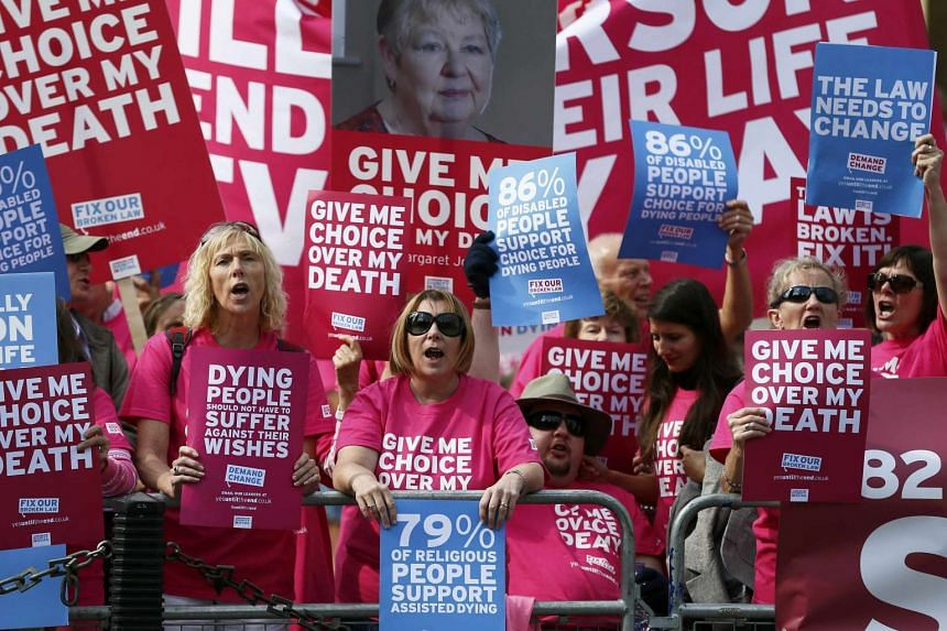 """Pro """"assisted dying"""" campaigners protest outside the Houses of Parliament in central London."""