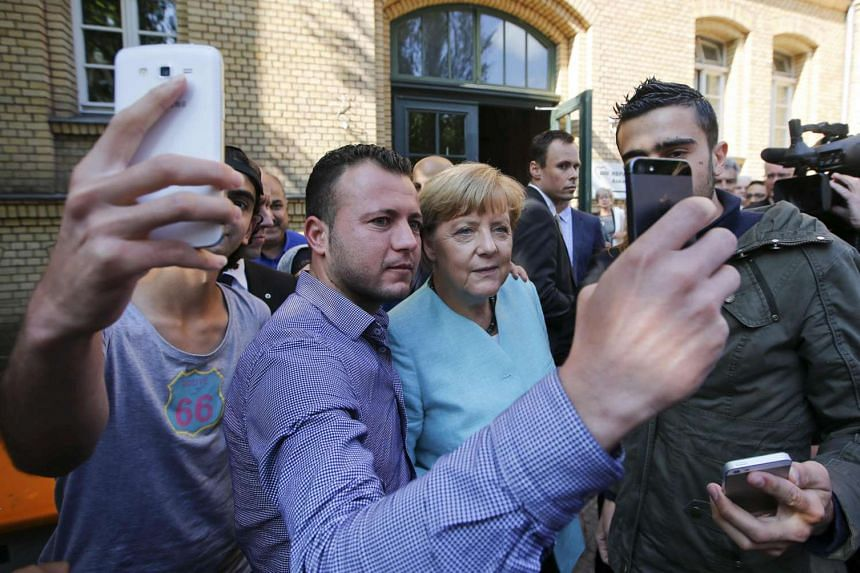 Migrants from Syria and Iraq take selfies with German Chancellor Angela Merkel.
