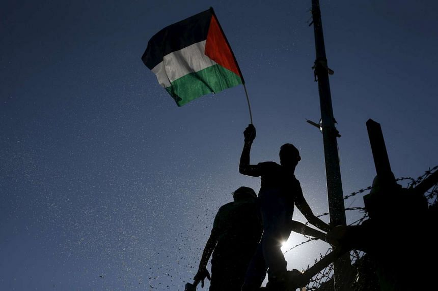 A spectator waves a Palestinian flag during the first leg of the Palestine Cup final soccer match between Gaza Strip's Shejaia and Hebron's Al-Ahly at al-Yarmouk stadium in Gaza City on Aug 6, 2015.