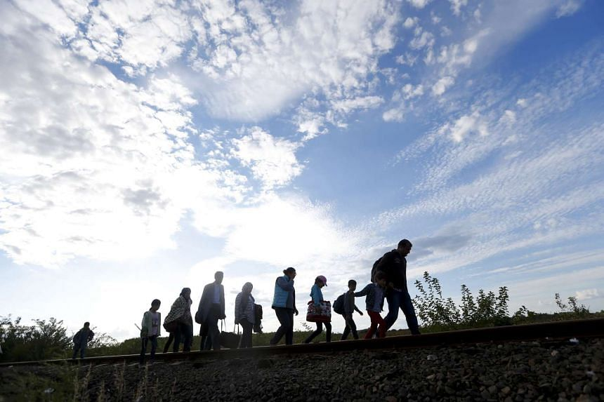 Migrants walking along rail tracks to a makeshift camp in the village of Roszke, Hungary, on Sept 7, 2015.