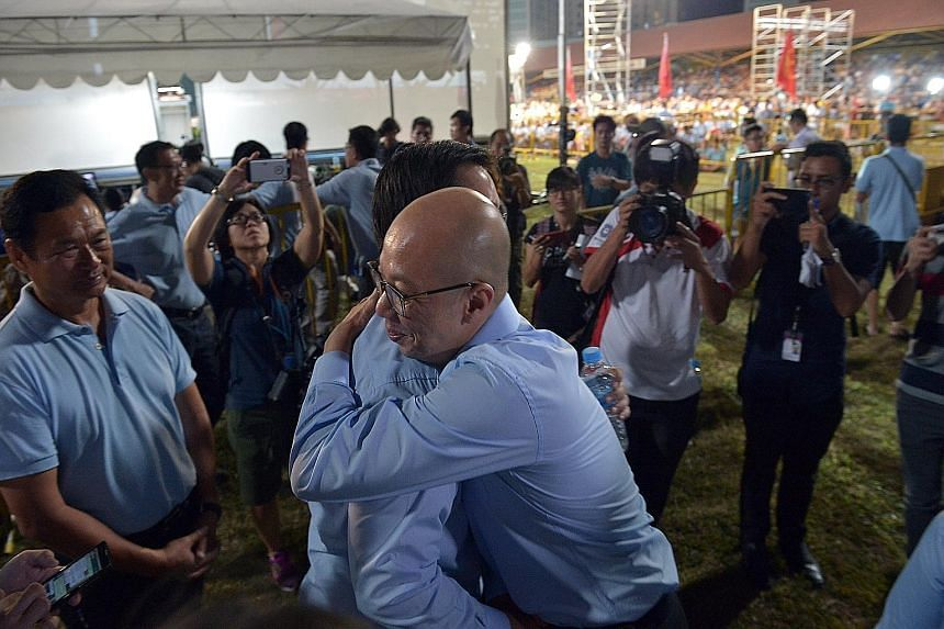 Workers' Party supporters giving Ms Lee Li Lian their support during her concession speech. She lost to the PAP's Charles Chong in Punggol East. WP candidate for Marine Parade Terence Tan (foreground) hugging Mr Ron Tan (candidate for Nee Soon) as th