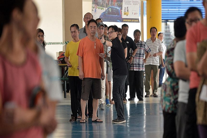 People waiting to cast their ballots at Pei Chun Public School in Toa Payoh Lorong 7 yesterday. At polling stations, many voters formed long lines long before the opening time of 8am. Candidates from various parties were also seen visiting various po