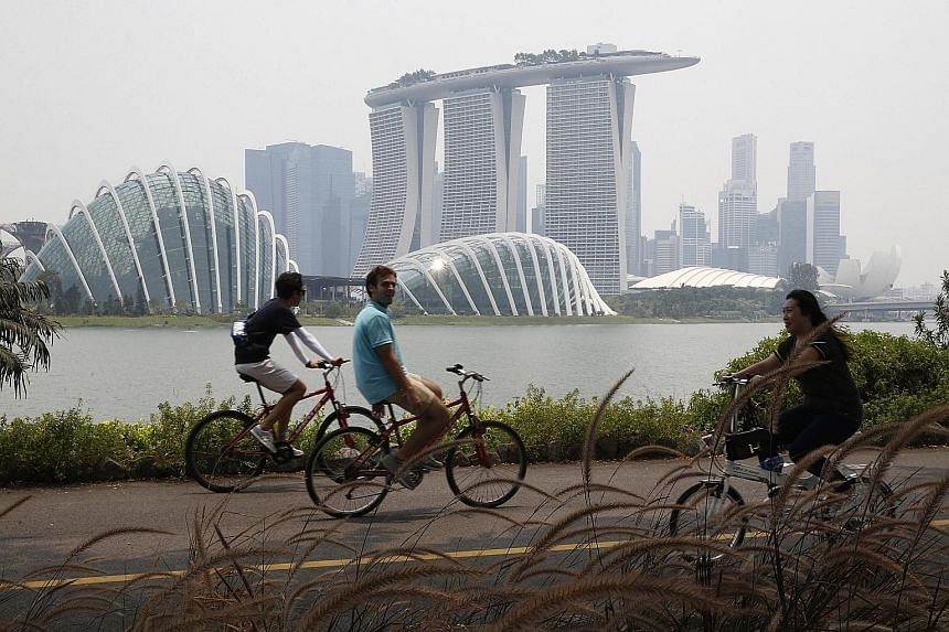 Cyclists at Bay East, Gardens by the Bay, at 1.15pm yesterday. The National Environment Agency has forecast the 24-hour PSI to be in the mid to low end of the unhealthy range. This may even move into the high end of the moderate range if winds stay f