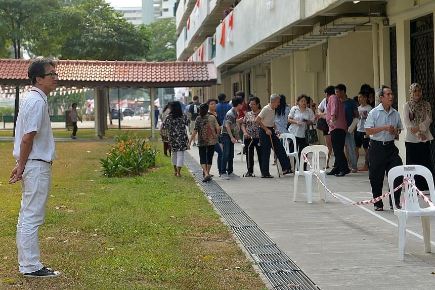 Mr Lim Swee Say looking at the voters at the New Upper Changi Road polling station yesterday.