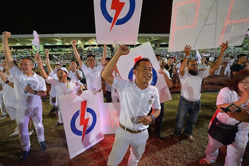 PAP supporters cheering at Bedok Stadium as they awaited the results last night.