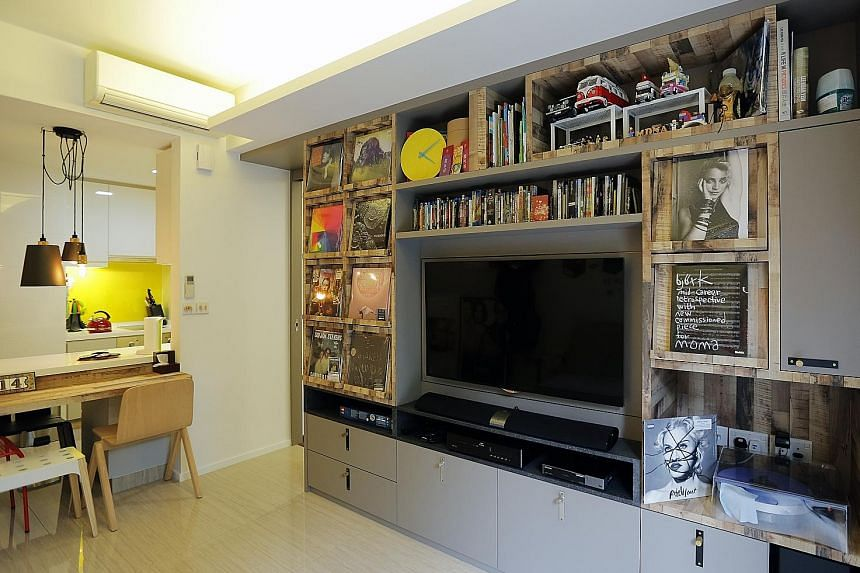 Customised display and storage spaces in the home of Mr Darrin Yok (above) help show off his record collection. (Left) His living room and dining area. A swivel wall for the television set lets the owner watch shows from the comfort of his bedroom (a