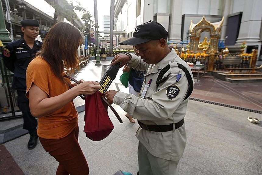 A security guard conducting checks at the Erawan Shrine this week. The investigation into the bomb attack has gained momentum with information given by one of two detained suspects.