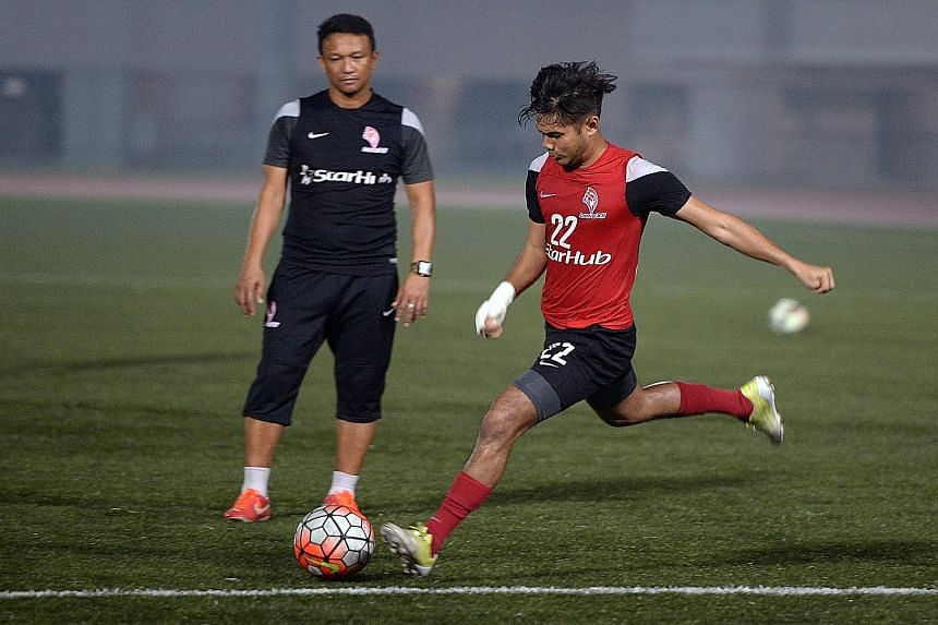 Christopher van Huizen taking a shot at training, watched by LionsXII coach Fandi Ahmad. Used chiefly as a substitute this season, the winger has the ability, says Fandi, to come on late in a game and make an impact.
