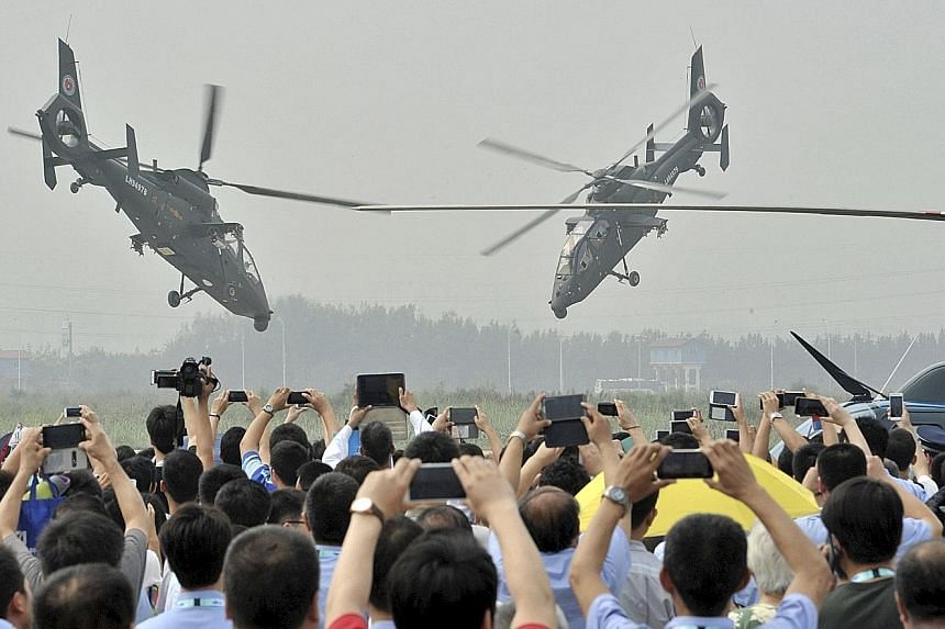 The People's Liberation Army helicopters performing during an aerobatic display at the China Helicopter Exposition on Wednesday in Tianjin. New helicopters will be added to the fleet by 2020.