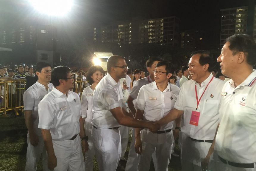 Mr Janil Puthucheary shaking hands with PAP's Punggol East candidate Charles Chong (with red tag) after he took back the single-seat ward from the Workers' Party in the 2015 General Election. With them are PAP Pasir Ris-Punggol candidates (from left)