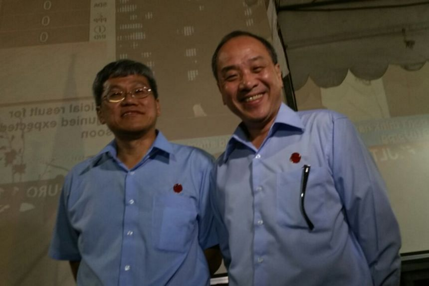 Re-elected Hougang MP Png Eng Huat (left) standing next to Workers' Party chief Low Thia Khiang at Hougang Stadium early in the morning on Sept 12, 2015.
