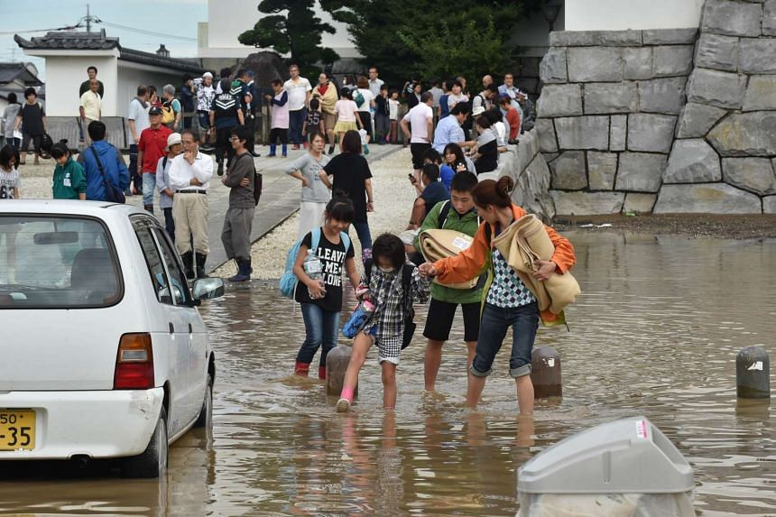 Residents walk on a flooded street after leaving a shelter in the city of Joso, in Ibaraki prefecture, on Sept 11, 2015.