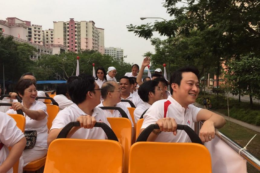 Sengkang West MP-elect Lam Pin Min (right) going around the estate on an open-top bus to thank residents.