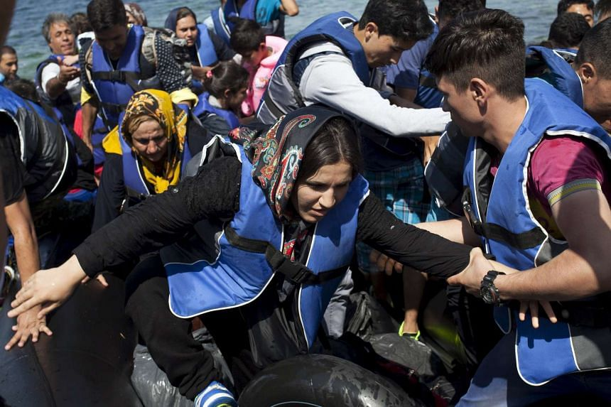 Refugees and migrants jump off a dinghy as they arrive on the Greek island of Lesbos on Sept 11, 2015.