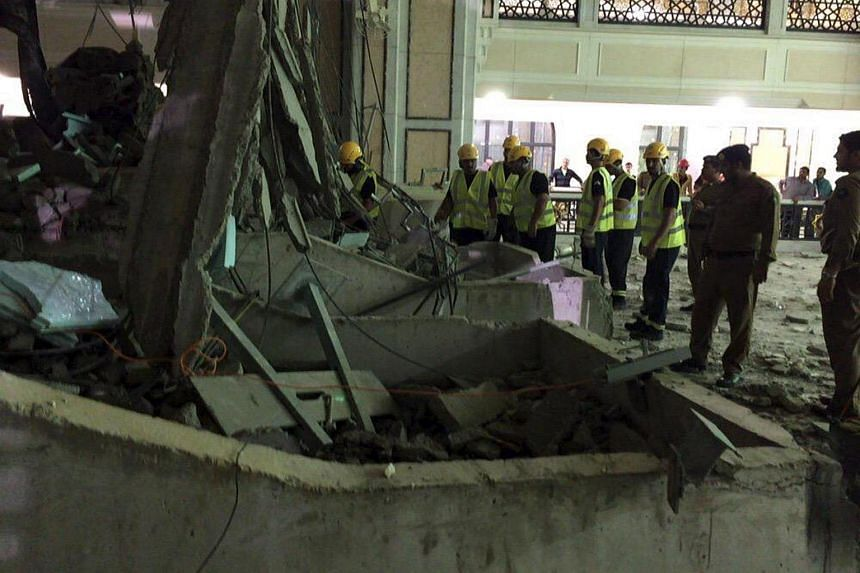 Members of a Saudi emergency crew stand near damage caused by a collapsed crane in the Grand Mosque in the Muslim holy city of Mecca, Saudi Arabia in this handout picture published on Twitter account of the Directorate of the Saudi Civil Defense on S