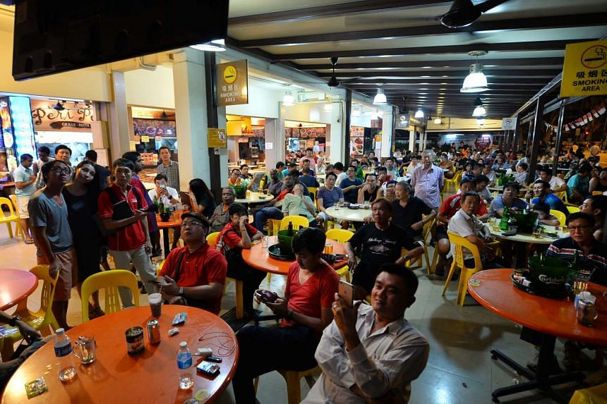 Customers at a coffee shop in Potong Pasir watching the election results on television.
