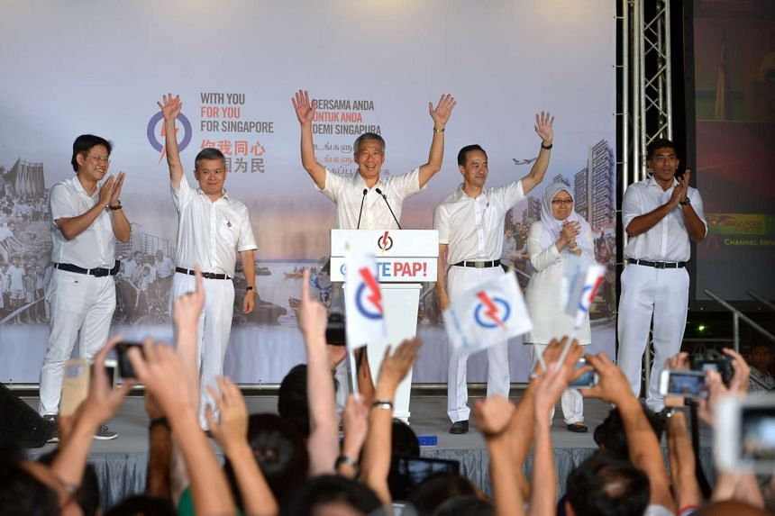 Prime Minister Lee Hsien Loong (third from left) and his Ang Mo Kio GRC teammates (from left) Gan Thiam Poh, Ang Hin Kee, Koh Poh Koon, Intan Azura Mokhtar and Darryl David thanking their supporters at Toa Payoh Stadium.