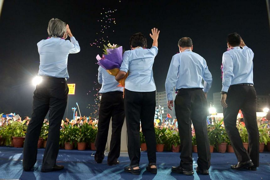 Candidates from the Workers' Party team for Aljunied GRC (from left) Chen Show Mao, Muhamad Faisal Abdul Manap, Sylvia Lim, Low Thia Khiang and Pritam Singh on stage thanking supporters at Hougang Stadium last night.