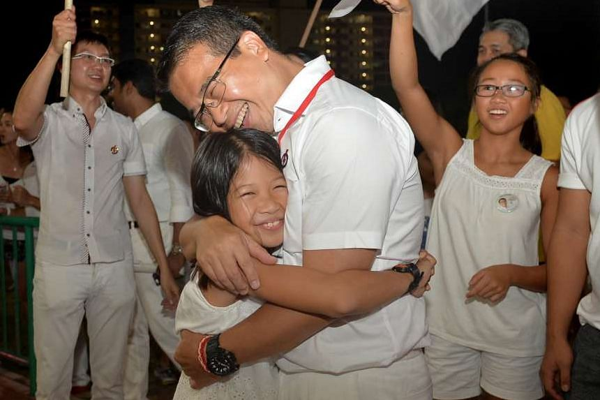 Mr Edwin Tong from the PAP team for Marine Parade GRC hugging his daughter Audrey, nine, as his elder daughter Claire, 14, cheered him on at Bedok stadium last night.