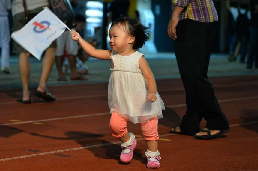 A young child waving a PAP flag jubilantly at Jurong West Stadium.