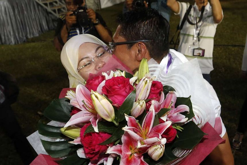Dr Mohamad Maliki Osman kissing his wife Sadiah Shahal as they celebrated the PAP's victory in East Coast GRC at Bedok Stadium.
