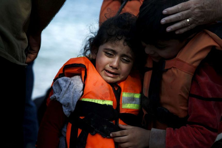 A Syrian refugee girl is comforted by her brother as she cries moments after arriving in a dinghy on the Greek island of Lesbos, on Sept 12, 2015.