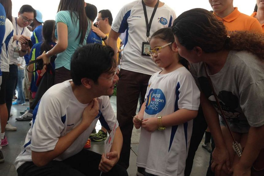 """Minister for Culture, Community and Youth Lawrence Wong buying a handmade card from Seet Jiaxin, 7, one of the young """"entrepreneurs"""" at the Kids' Bazaar at the Marina Bay Promontory on Sept 13, 2015."""